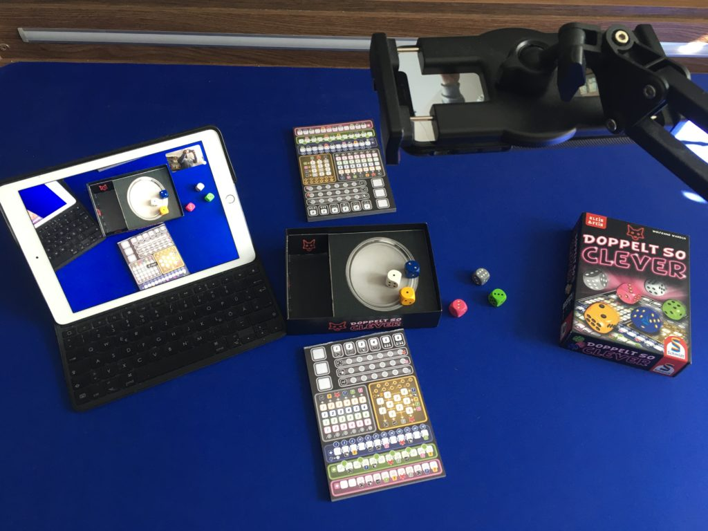Tisch mit Monitor, Handyhalterung und Brettspiel